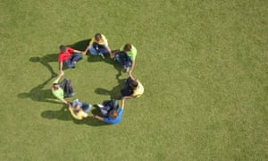 children sitting on grass in circle formation