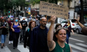 """A woman holds a placard reading in French """"Never in my body the liquid of dictature shall enter""""."""