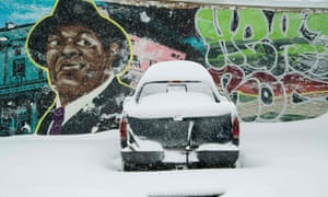 A pickup truck is covered in snow in front of a mural of late Former Washington mayor Marion Barry during a snowstorm in Washington, DC, on Saturday.
