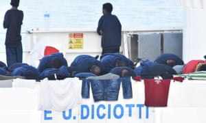 Migrants pray on a ship