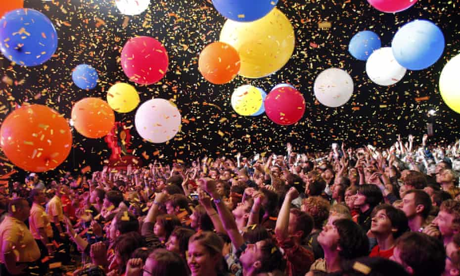 Festivalgoers at a gig in Katowice, Poland, as part of the OFF festival. Colourful balloons hover above the crowd, with ticker tape showering down.