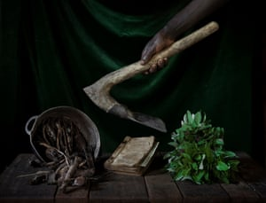 A table in Marie Mbendu's house, Bossembélé, with amaranth leaves, a pot full of 'termite' wood, a hymn book and a hoe