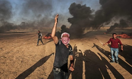 Palestinian protesters demonstrate during clashes with Israeli security forces near the border
