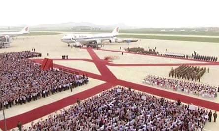 A plane with the Chinese president, Xi Jinping, onboard arrives at Pyongyang's airport. Reports said 10,000 people welcomed Xi alongside Kim Jong-un.
