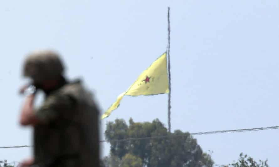 A Turkish soldier stands on an armoured personnel carrier as in the background a flag of the Kurdish YPG units is raised over the town of Tal Abyad, Syria, on Tuesday.