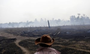 A farmer walks on a smouldering field after it was hit by a fire burning a tract of the Amazon forest in Rio Pardo, Rondonia, Brazil 16 September 2019.