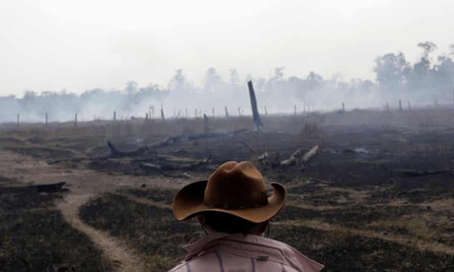 A farmer next to a smouldering field after it was hit by a fire in Rio Pardo, Rondonia, Brazil 16 September 2019.