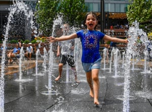 A young fan runs through a fountain to cool off before the game between the Chicago Cubs and the San Diego Padres at Wrigley Field