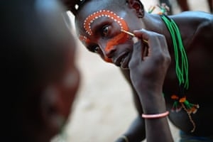 A Hamar man has his face painted before a bull jumping ceremony