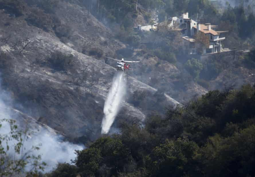 A helicopter drops water as the Getty fire burns on Kenter Canyon in Los Angeles.