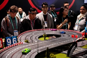 Visitors test Brainco's model race cars racing using their brainwaves to make the cars start and accelerate