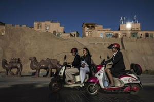 Uyghurs ride past a newly finished section of the old city walls