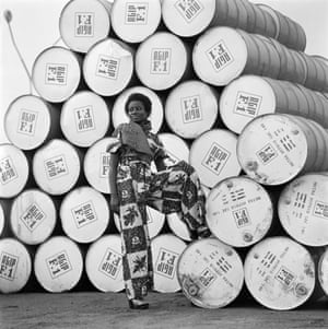 A woman stands in front of barrels