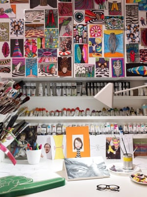 Elie's studio with a montage of postcard-size pictures on the wall, rows of paint tubes and brushes