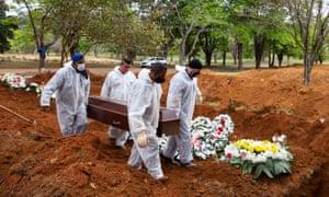 Cemetery workers in protective suits bury Elisa Moreira de Araujo, 79, a victim of coronavirus in Sao Paulo, Brazil.
