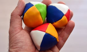 Man holds three (3) Juggling balls on one hand (left) against light background. concept photo, copy spaceE3YPH8 Man holds three (3) Juggling balls on one hand (left) against light background. concept photo, copy space