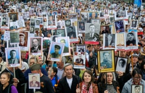 Locals carry photos of relatives killed in the war during a parade in Almaty, Kazakhstan
