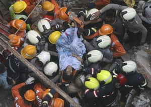 Rescuers carry out a survivor from the site of a four-storey building that collapsed in Mumbai, India.