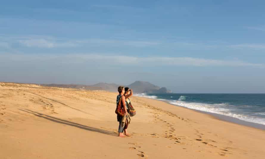 Two women walk along the beach at Todos Santos, Baja California, Mexico.