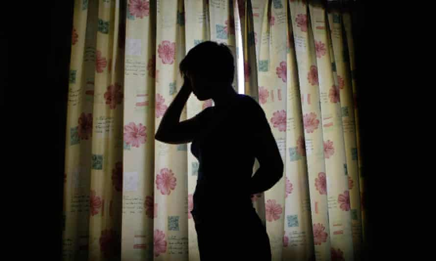 A silhouetted woman holds her head in her hands