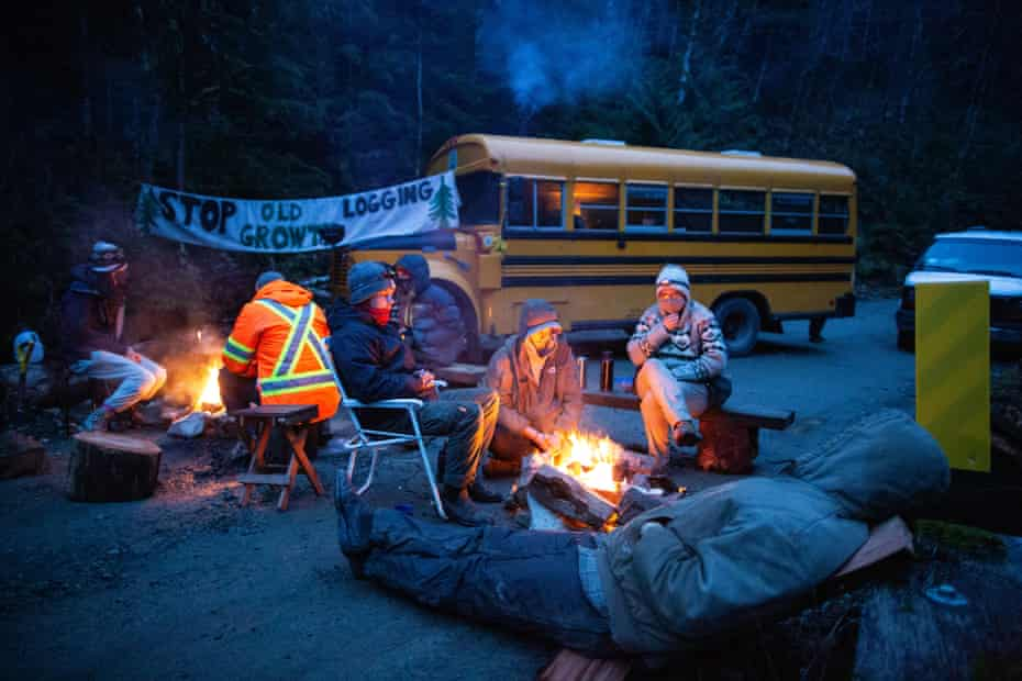 Members of the Rainforest Flying Squad blocking a logging road stay warm around a fire after setting up a new blockade.