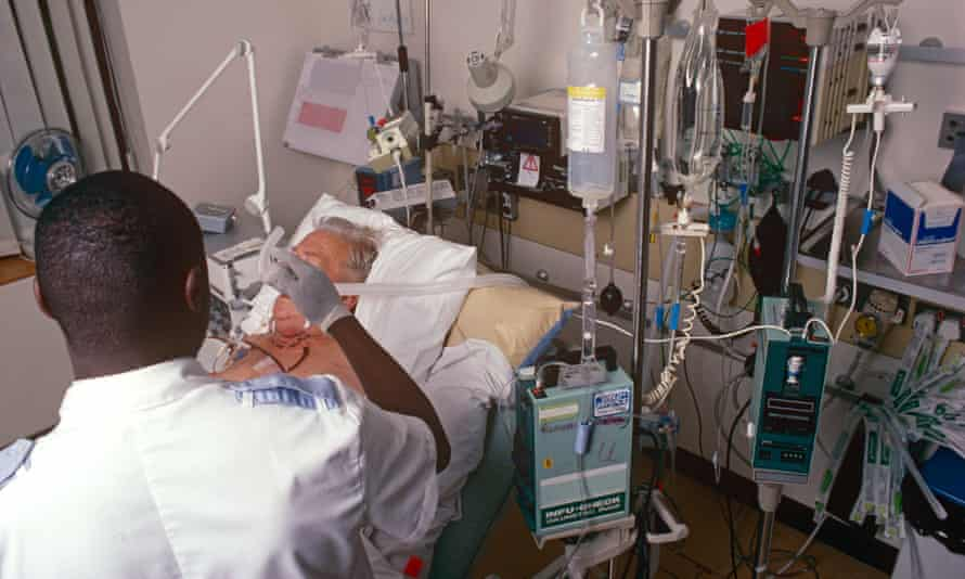 A male staff nurse giving oxygen to a patient in the intensive care unit of a London Hospital