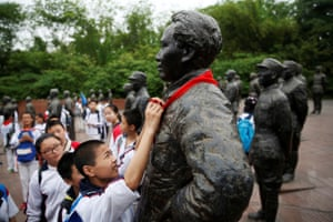 A student puts a red scarf on a statue of Mao