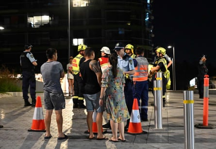 Police check the unit numbers of the residents after an inspection of the Opal Tower to determine whether it is safe for them to return.