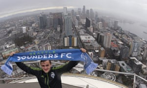 Jordan Morris with Sounders scarf atop the Space Needle in Seattle.