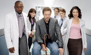 Hugh Laurie holding a cane and being wheeled on a gurney next to the original cast of House – Omar Epps, Jennifer Morrison, Hugh Laurie, Robert Sean Leonard, Jesse Spencer, Lisa Edelstein