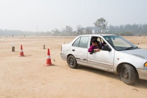 Twenty-eight-year-old Pushpa tries to park the car within the red cones during a reverse parking exercise.