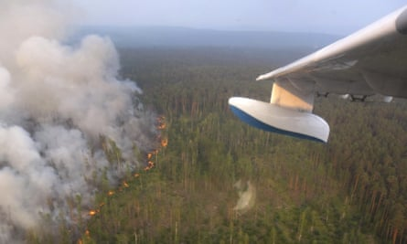 A jet prepares to pour water on to a forest fire in Krasnoyarsk, Russia.
