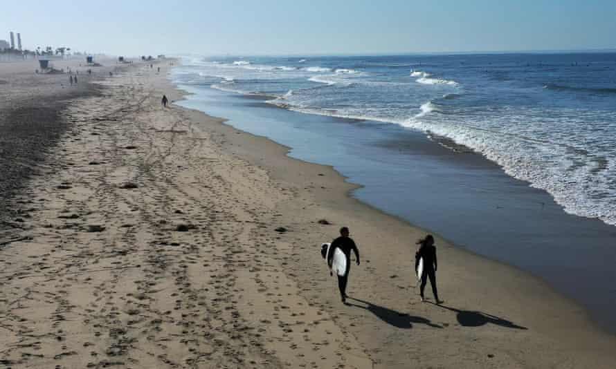 Surfers enjoy a cloudless morning at Huntington Beach, California.