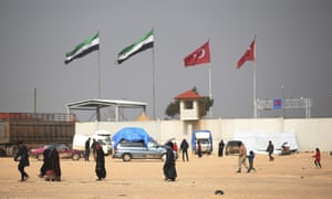 People walk on the Syrian side of the Bab al-Salam border crossing with Turkey.