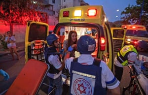 Rescue workers evacuate a woman by ambulance, amidst a rocket attack from the Gaza Strip, in the southern Israeli city of Sderot