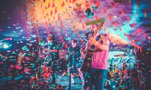 Band perform on stage amid tickertape at Camp Wildfire festival, Kent, UK.