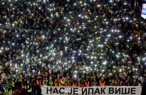 Anti-government protesters hold up their phones and candles, as well as a banner, during a march in Belgrade, Serbia