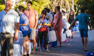 Residents queue to fill plastic water bottles and containers at a spring in Cape Town, South Africa.