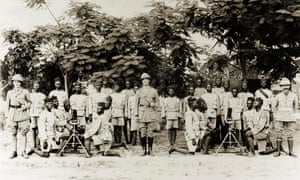 Three British officers pose with an artillery company of the Nigeria Regiment of the Royal West African Frontier Force, 1918.