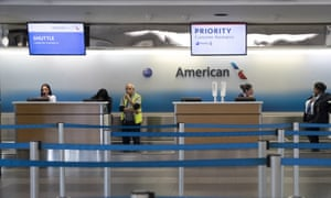American Airlines employees wait for passengers to check in at Laguardia airport in New York city