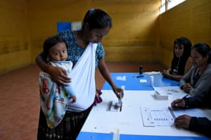 An indigenous woman holding a baby casts her vote during runoff elections in Santa Cruz Chinautla, Guatemala,