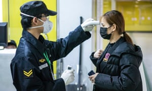 A security guard checks a passenger's body temperature at the entrance of a subway station in Guangzhou, Guangdong province