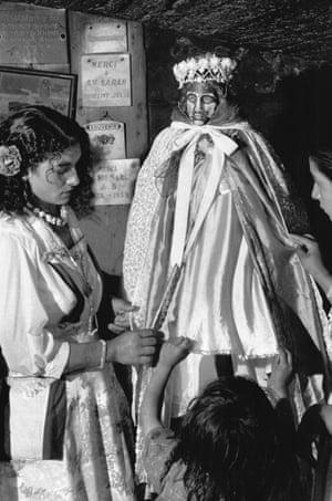 Roma girls dress a statue of St Sarah at Saintes-Maries-de-la-Mer.