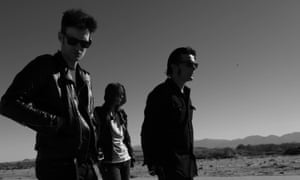 black rebel motorcycle club standing in the desert in their jackets and sunglasses