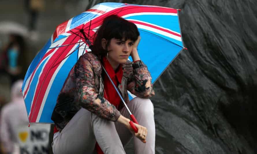 A woman shelters under a Union flag umbrella