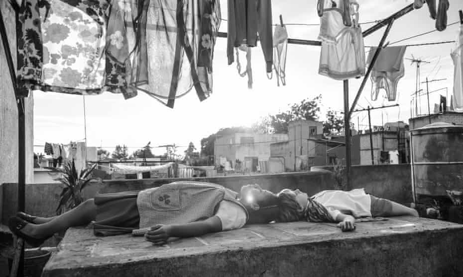 A scene from Roma of a young girl and boy lying on a Mexico City rooftoop amid laundry hanging on lines and the sun breaking through.