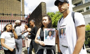 Melani Urbano holds up a picture of her sister Jessica who remains missing following the blaze at Grenfell Tower