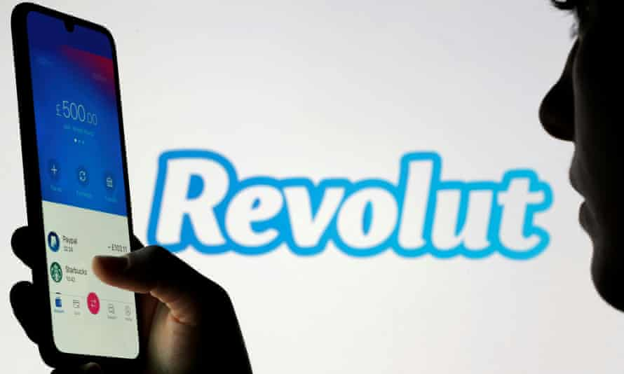 Woman holds smartphone with Revolut app in front of displayed Revolut logo