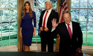 Sean Spicer poses next to wax figures of Melania and Donald Trump, at Madame Tussauds in New York City.