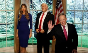 Sean Spicer poses next to wax figures of Melania and Donald Trump in New York City on 25 April. The living Donald Trump's recommendation of his book? 'Really good, go get it!'